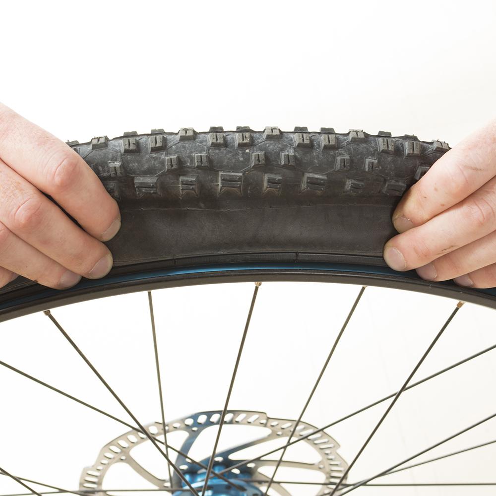 Repoussez les 2 tringles du pneu vers le centre de la jante